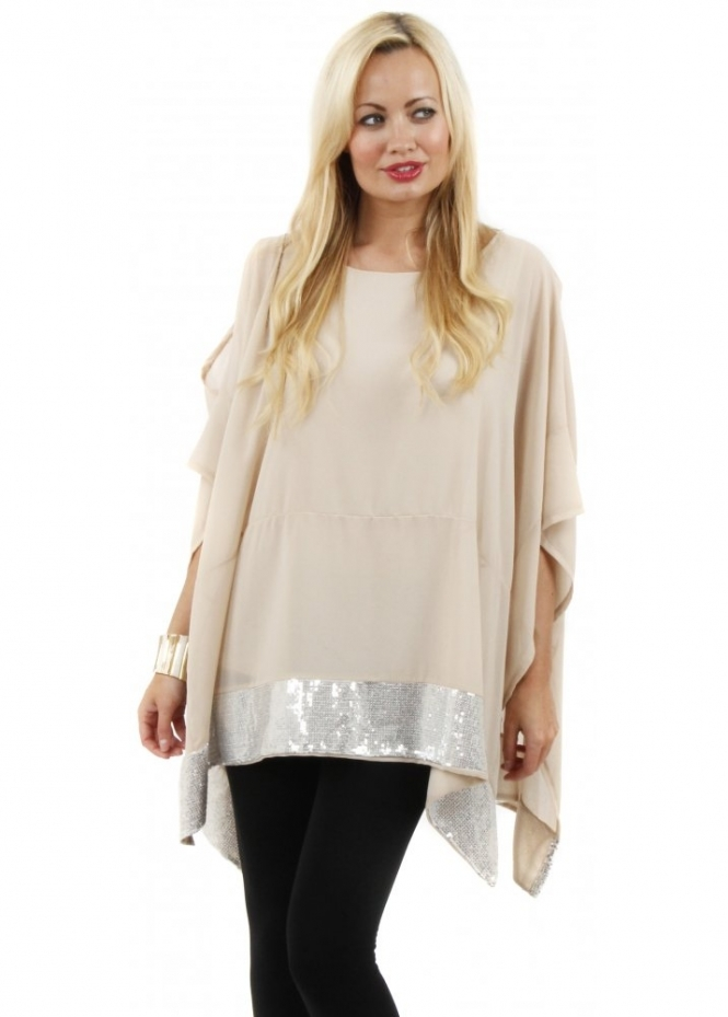 This stylish tunic top features a beautiful winter design of blue and cream poinsettias and white snowflakes on a light blue background, 3/4length sleeves, scoop neckline, sparkling sequin details and a modern highlow hemline.